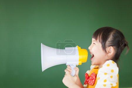 Photo pour Heureux enfant crie quelque chose dans le mégaphone - image libre de droit