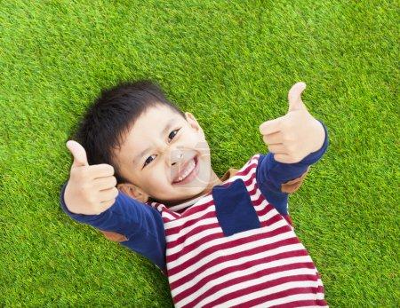 Foto de Niño sonriente mintiendo y pulgar para arriba en un prado - Imagen libre de derechos