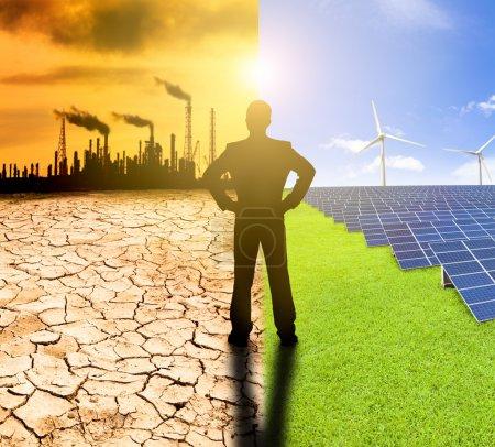 Foto de Contaminación y concepto de energía limpia. hombre de negocios viendo molinos de viento paneles solares y refinería con contaminación del aire - Imagen libre de derechos