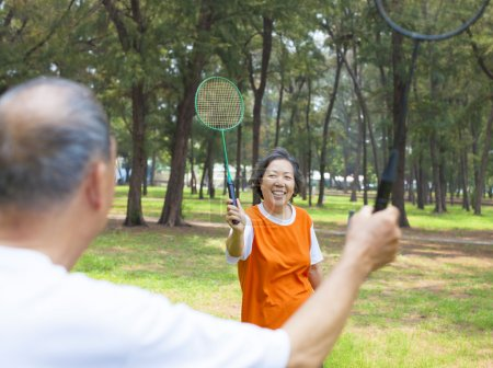 Senior couple or friends playing badminton in the park