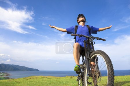 Photo for Young man sitting on a  mountain bike and open arms to relaxing - Royalty Free Image