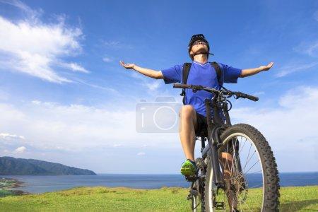 Photo pour Jeune homme assis sur un vélo de montagne et ouvrir les bras pour se détendre - image libre de droit