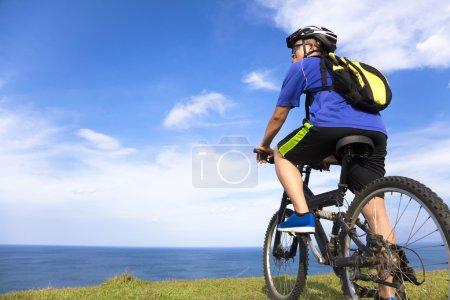 Photo pour Jeune homme assis sur un vélo de montagne et à la recherche de l'océan - image libre de droit