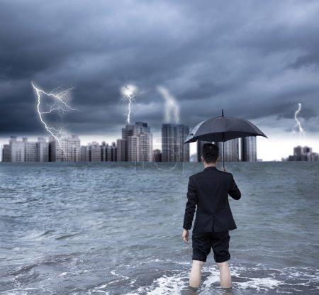 Photo pour Homme d'affaires tenant un parapluie avec fond orageux - image libre de droit