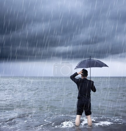 Photo pour Bouleversé homme d'affaires tenant un parapluie avec fond nuageux - image libre de droit