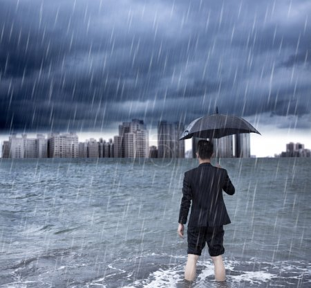 Photo pour Homme d'affaires tenant un parapluie et debout avec fond nuageux - image libre de droit