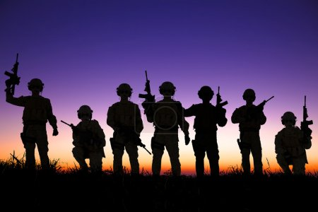 Soldiers silhouettes against a sunset or sunrise b...