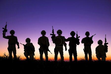Photo pour Silhouette de l'équipe de soldats avec fond de lever de soleil - image libre de droit