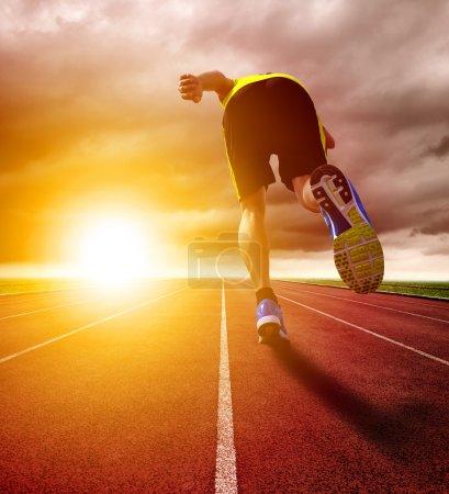 Photo pour Athlétique jeune homme en cours d'exécution sur la piste de course avec fond coucher de soleil - image libre de droit