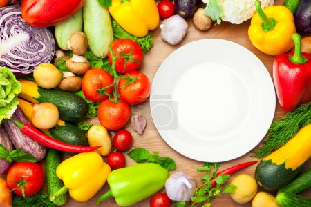 Photo for Fresh Organic Vegetables on wooden Table Around White Plate / with copy space for your text - Royalty Free Image