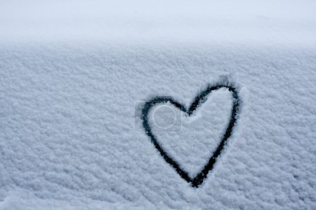 Heart shape love symbol for valentine day drawn on white snow