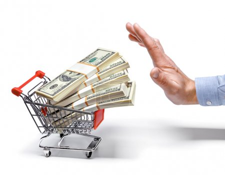 Photo pour Man's hand stops the cart full of money stacks - isolated on white background - image libre de droit