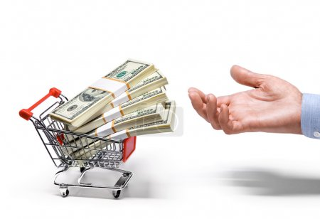 Businessman's hand & shopping cart full of stacks of american dollar banknotes - isolated on white background