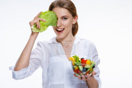 Photo for Comic girl of the european appearance closes an eye with cabbage leaf and holds dieting vegetable salad in transparent crockery - isolated on white background - Royalty Free Image