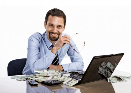 Successful smiling businessman with a lot of dollar stacks at the desk isolated on white background