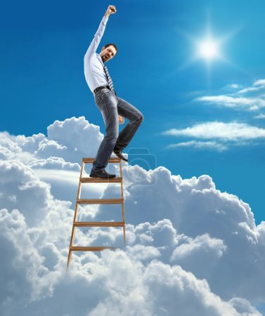 Young confident businessman standing at the ladder high in the sky reaches the top