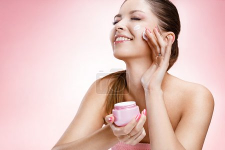 Young beautiful girl with a face cream