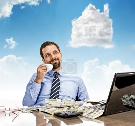 Daydreaming businessman with a cup of tea with head in the clouds