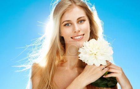 Photo pour Portrait de jeune fille souriante heureuse avec une fleur blanche dans ses mains sur fond bleu - image libre de droit
