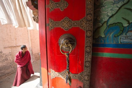 Young monk in front of the entrance of a temple