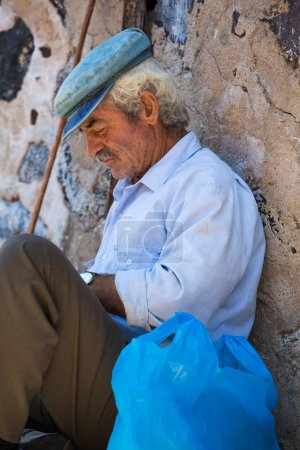 Man sitting quietly against a wall and protecting himself from t