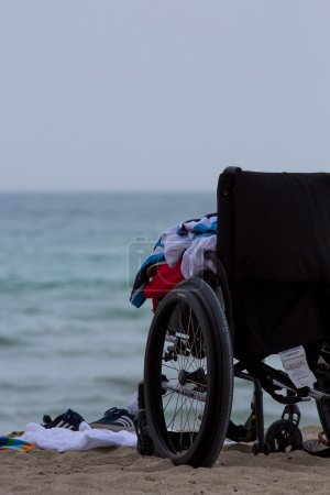 Empty wheel chair on the beach with clothes