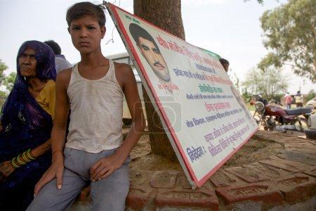 Photo pour AGRA, INDE, 18 JUILLET : Vieille femme non identifiée et un jeune enfant assis et attendant leur tour pour une visite médicale gratuite avec un panneau d'information politique en arrière-plan . - image libre de droit