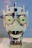 Head of a robot with funny green eyes and a funny expression