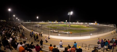 People watchting a stock car competition at night