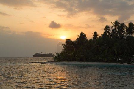 Sunset, ocean and coconut trees near paradisiac island