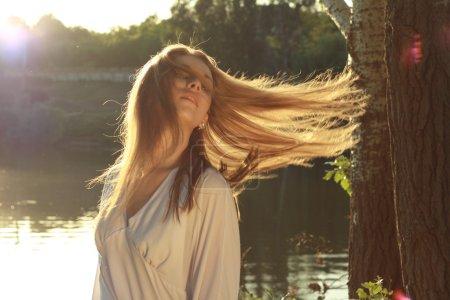Photo pour Gros plan d'une jeune femme souriante avec mouche cheveux sur cheveux extérieur fond clair. couleurs de l'été - image libre de droit