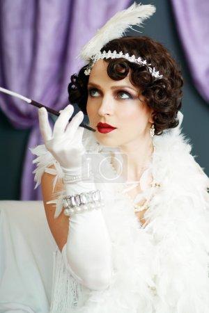 Photo pour Fille rêvant belle jeune femme battant dame des années 20 rugissant en regardant la caméra. Teinte bleue sur l'image . - image libre de droit