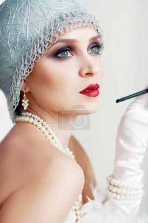 Photo pour Fille rêvant belle jeune femme battant des années 20 rugissant en regardant la caméra. Teinte bleue sur l'image . - image libre de droit