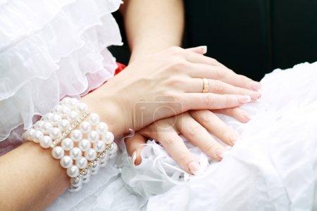Photo pour Mariée de mains avec une manucure, sur le doigt de l'anneau de mariage mariée, mains sur le fond de la dentelle blanche robe extérieures. fond mariage. - image libre de droit