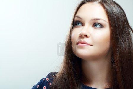 Photo pour Portrait de belle adolescente souriant sur fond gris regardant vers l'espace de copie - image libre de droit