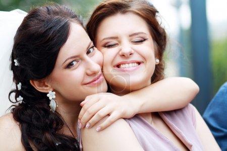 Bride and bridesmaid outside happy hug...