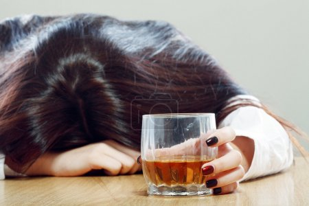 Photo for Woman holding an alcoholic drink and sleeping with her head on the table - Royalty Free Image