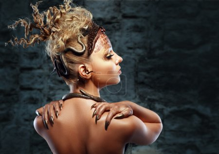 Gorgon medusa. Young woman with creative fantasy hairstyle and make up