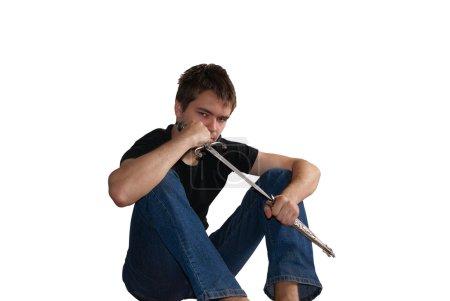 Foto de Joven sentada en el piso y mantiene cuchillo afilado - Imagen libre de derechos