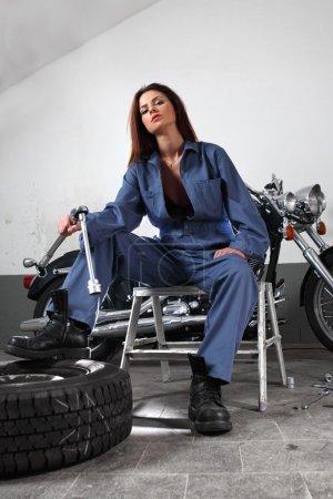 Photo pour Photo d'une belle mécanicienne travaillant sur une moto vêtue d'une combinaison et tenant un grand cliquet . - image libre de droit