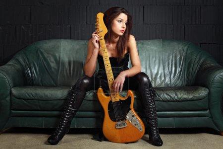 Photo pour Photo d'un joueur de guitare de femmes sexy portant des bottes en cuir et assis sur le vieux divan en cuir. - image libre de droit