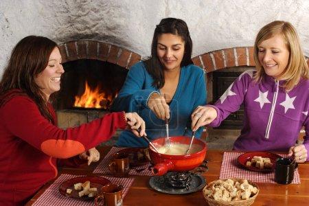 Photo pour Photo de trois belles femelles tremper le pain dans le fromage fondu dans un appareil à fondue. - image libre de droit