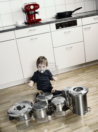 Photo for Photo of an adorable young boy using wooden spoons to bang pots and pans that are set up like a drumset. Desaturated and contrast increased. - Royalty Free Image