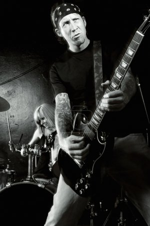 Photo for Photo of a female drummer and male guitarist playing on a stage. Slight motion blur on performers. - Royalty Free Image