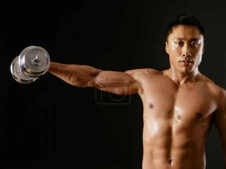 Photo for Photo of an Asian male exercising with dumbbells and doing shoulder flys or lateral flys over dark background. - Royalty Free Image