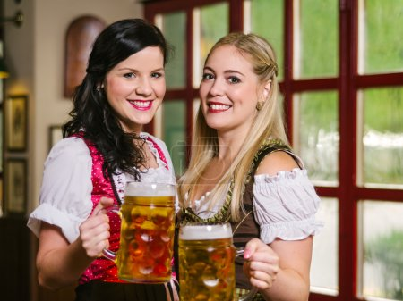 Photo for Photo of two beautiful female waitresses wearing traditional dirndl and holding huge beers in a pub. - Royalty Free Image