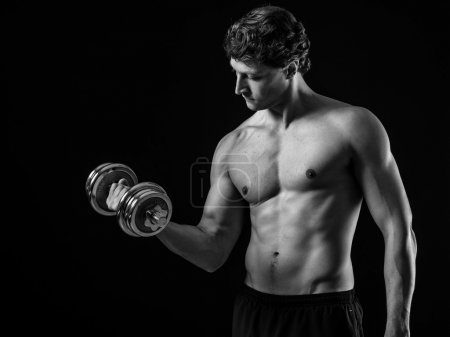 Photo for Photo of a man in his early thirties doing bicep curls with a dumbbell over a black background. Black and white version. - Royalty Free Image