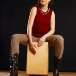 Photo of a beautiful young woman playing a Cajon p...