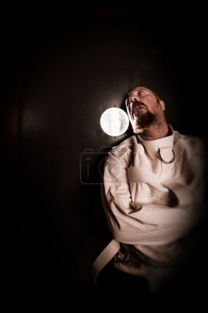 Photo for Photo of an insane man in his forties wearing a straitjacket standing in a cell of an asylum with the light from the hallway streaming in. - Royalty Free Image
