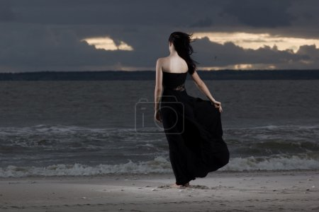Beautiful brunette model in long black dress standing on the beach. Cloudy weather. Sunset